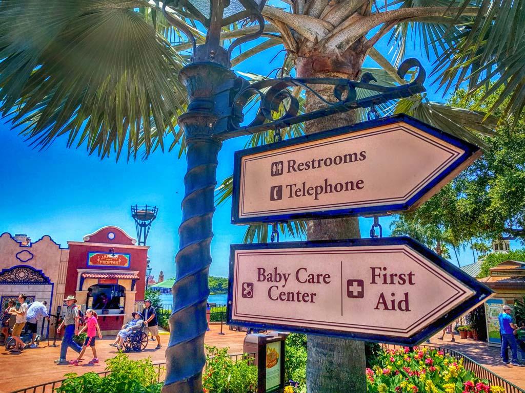 Placas indicativas no Epcot mostrando o caminho para os banheiros, a área de Primeiros Socorros (First Aid), e também o Baby Care Center