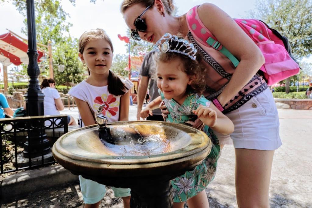 Tomando água em um bebedouro na Fantasyland, no parque Disney's Magic Kingdom